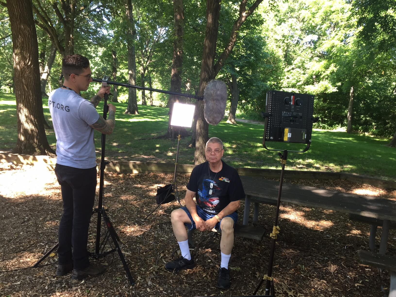 Man being interviewed in a park.