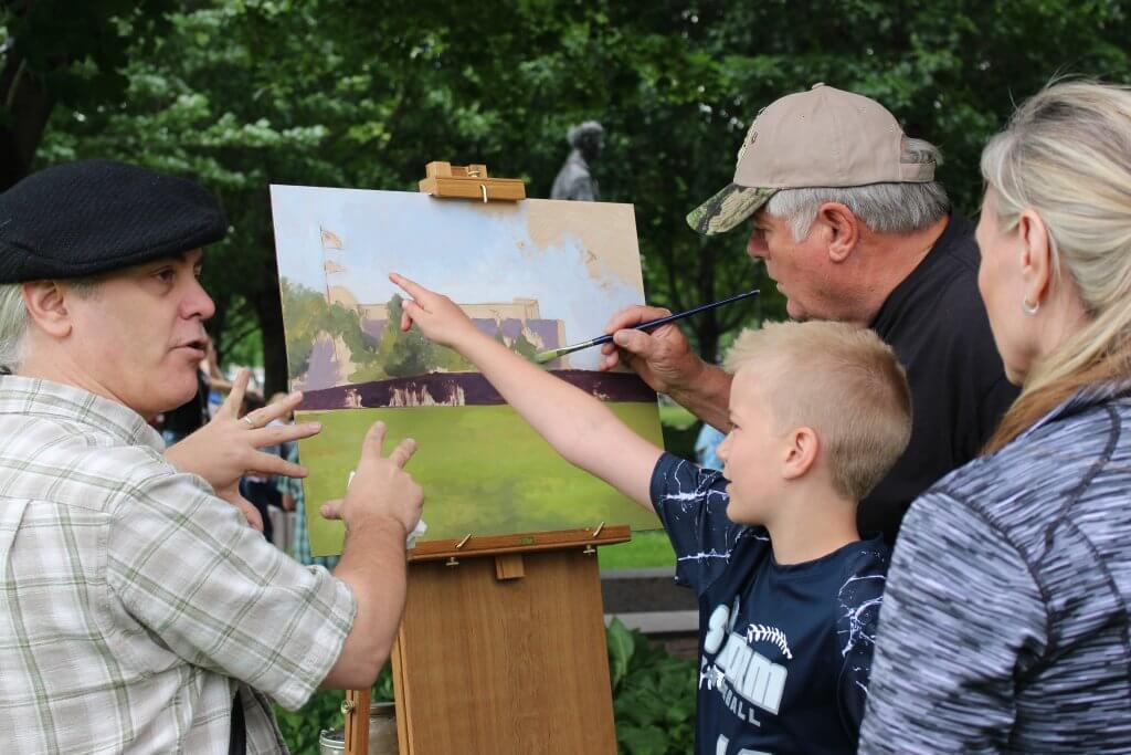 Group of people painting on a canvas outside.