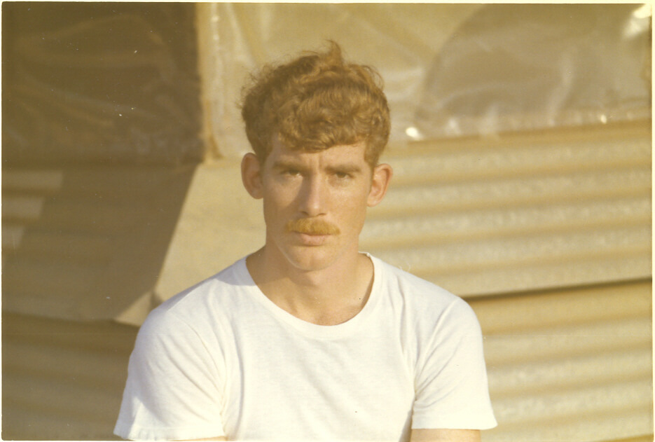 Soldier in a white tee shirt looking at camera