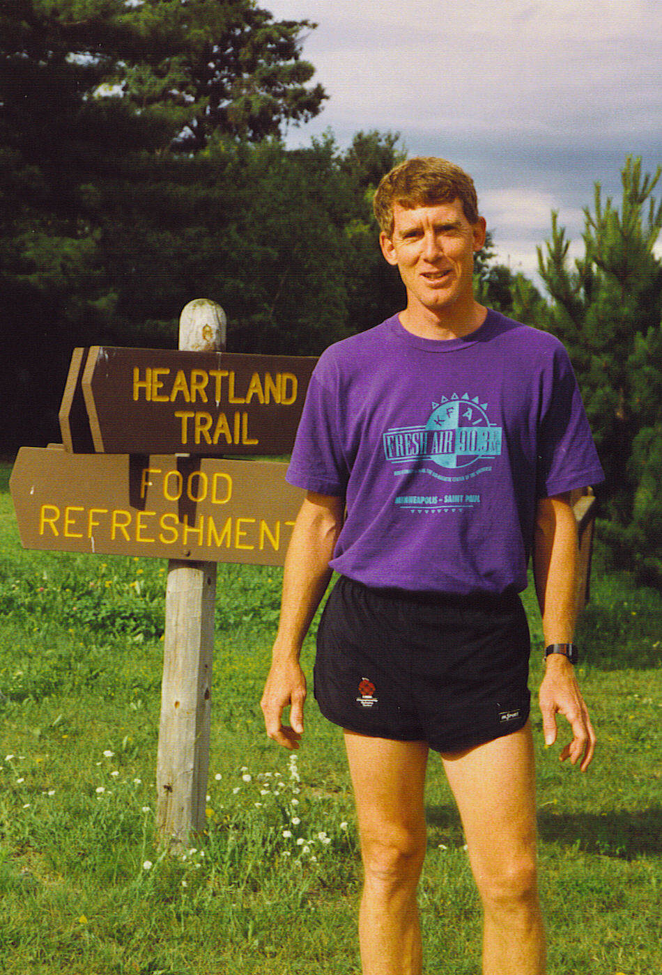 Man in running gear by a trail sign