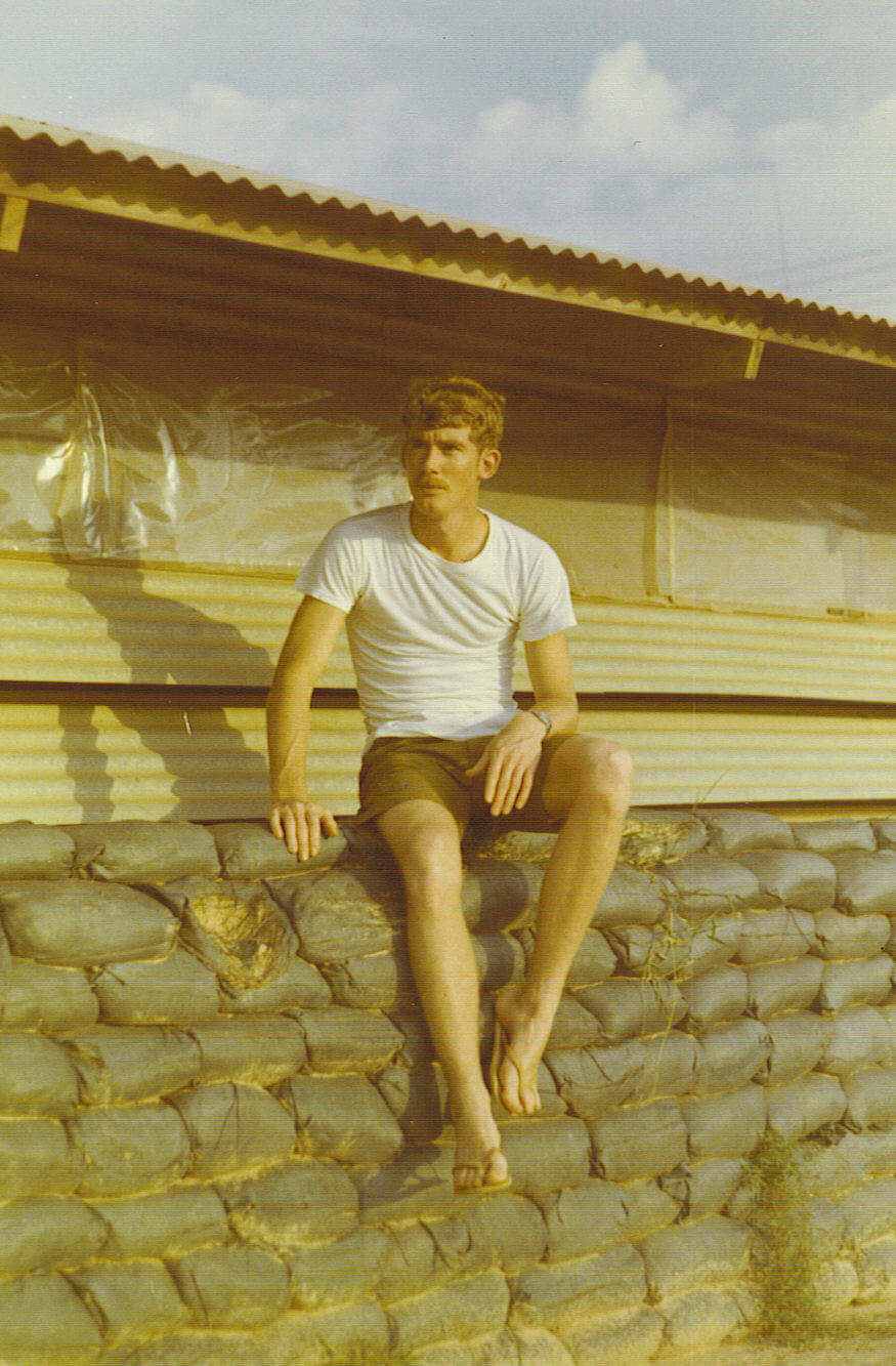 Soldier in a t-shirt and shorts sitting on top of sandbags in a military camp